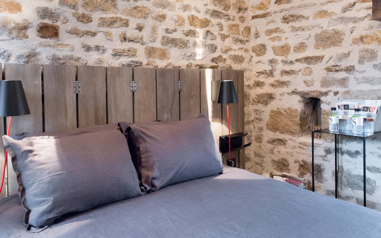 lit double avec tête de lit en bois et couvertures violettes et mur en pierre nuit romantique Dijon