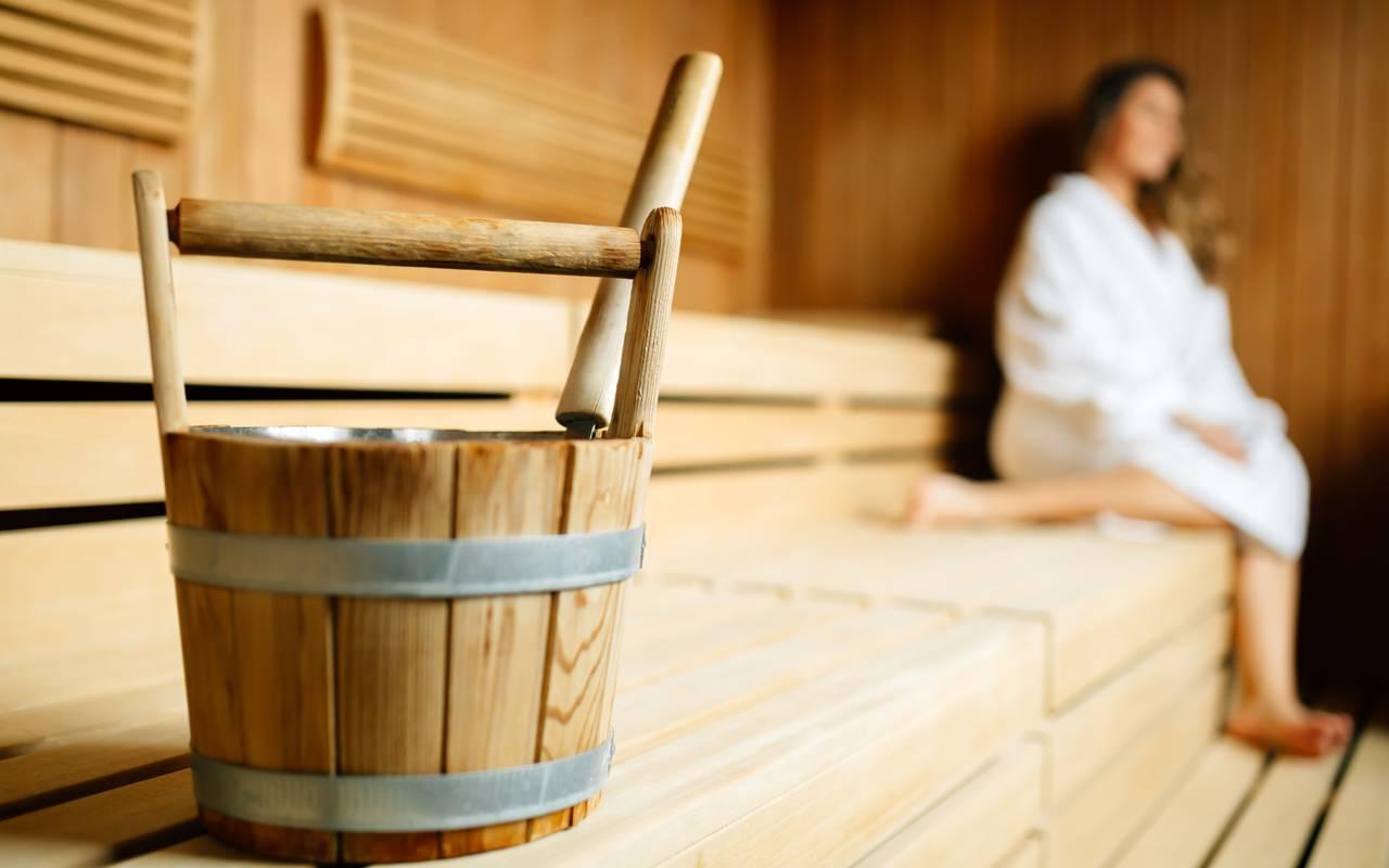 seau de sauna en bois avec dame en arrière plan spa Bourgogne